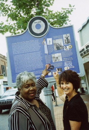 Dorothy Moore shows Central MS Blues Society member, Peggy Brown, her early points of career interests on the Blues Trail Marker unveiled at the Alamo Theater, Jackson, MS, May 22, 2008.